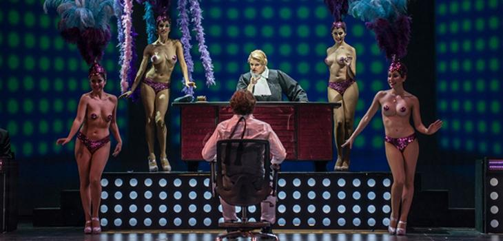 Escena del Juicio a Jimmy (Nikolai Schukoff) de espaldas frente a la Jueza Begbick (Susanne Resmark) y bailarinas. foto biobiochile